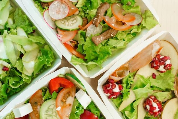 Groene natuurlijke salades in eco thermobox met microgroen, kalfsvlees, komkommer, tomaat, kaas. veiligheidslevering bij quarantaine covid 19.