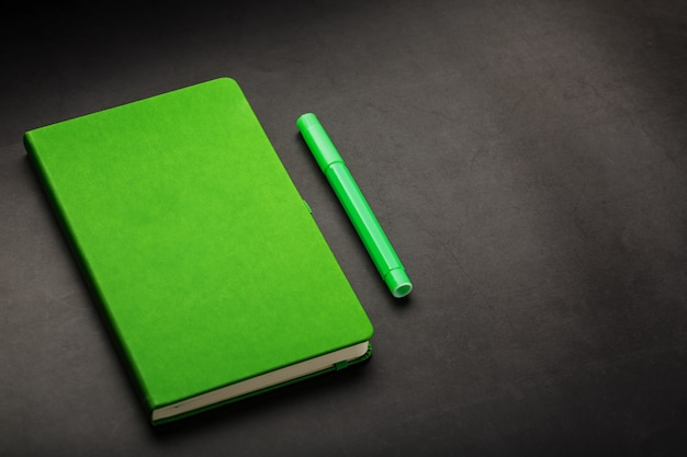 Groene notitieblok met een viltstift bovenaanzicht.