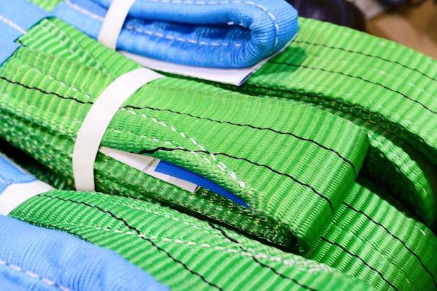 Groene nylon zachte hijsstroppen gestapeld in stapels. magazijn van afgewerkte producten voor industriële ondernemingen