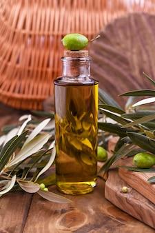 Groene olijven in blikjes met brood van vers brood en jonge olijven tak, fles olijfolie op klei bord over oude houten achtergrond. ruimte voor tekst