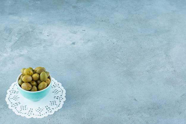 Groene olijven in een kom op een onderzetter, op de marmeren tafel.