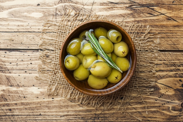 Groene olijven in houten kommen op houten tafel