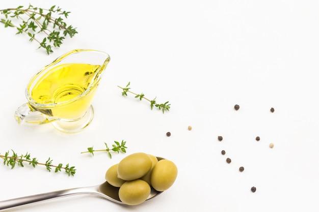 Groene olijven in metalen lepel. olijfolie in glazen pot. tijm takjes. bovenaanzicht.
