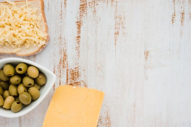 Groene olijven in witte kom; geraspte kaas op brood over het witte bureau