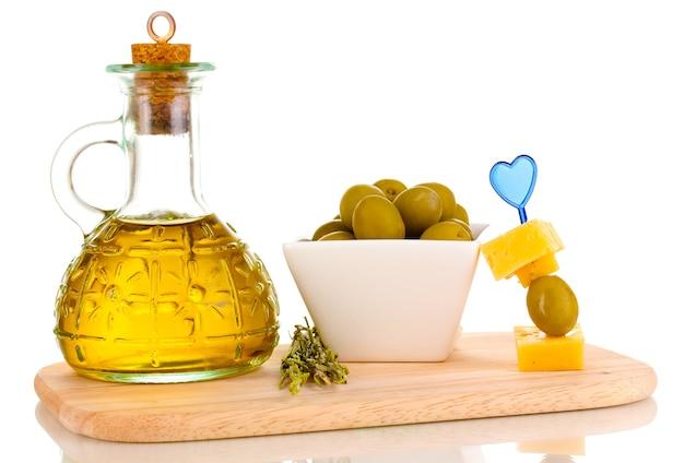 Groene olijven in witte kom met rozemarijn, olijfolie en kaas aan boord op wit wordt geïsoleerd