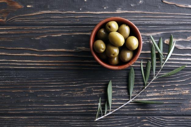 Groene olijven met een pit in een kom op een houten ondergrond. ruimte voor tekst. olijfboom. olijftak.