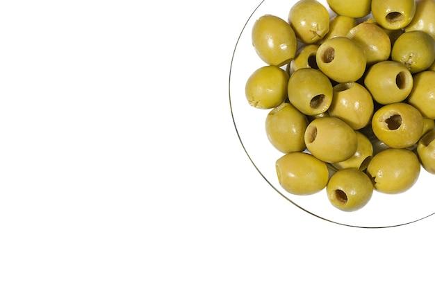 Groene olijven zonder pit op een transparante glazen plaat (van bovenaf gezien)