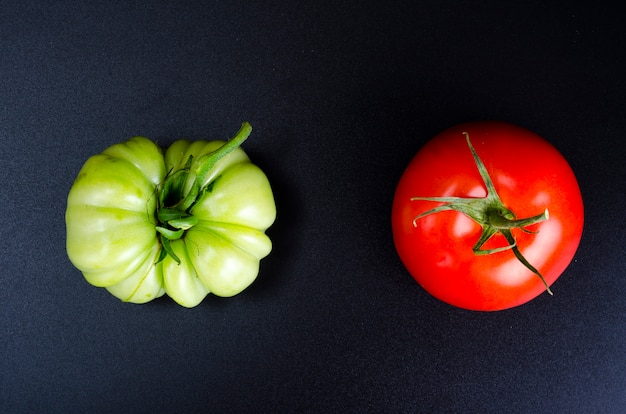 Groene onrijpe tomaat op zwarte achtergrond