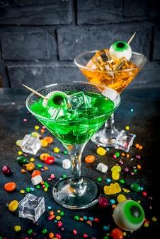 Groene, oranje martini-cocktail met ijsblokjes en een decor van marshmallow-ogen