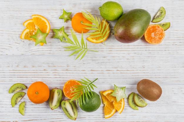 Groene palmbladeren en verse tropische plakjes fruit op witte houten tafel