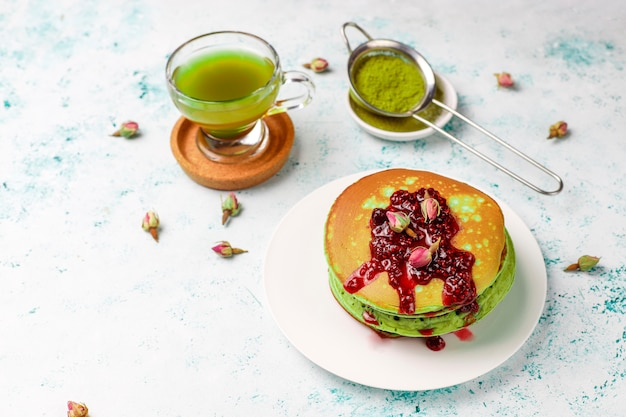 Groene pannenkoeken met matcha poeder met rode jam, bovenaanzicht