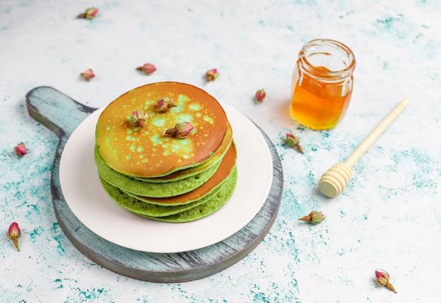 Groene pannenkoeken met matcha poeder met rode jam op lichte tafel