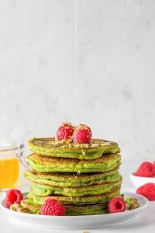 Groene pannenkoeken met matcha-thee, frambozen, pistachenoten en honing. gezond ontbijt. verticale oriëntatie