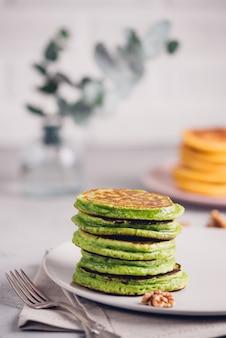 Groene pannenkoeken met matcha-thee of spinazie, opgemaakte honing en rode druiven