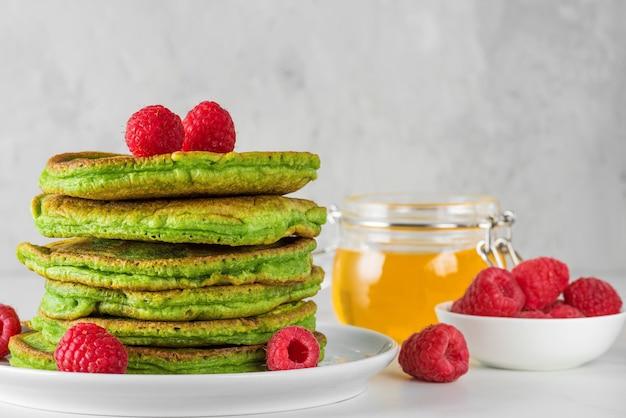 Groene pannenkoeken met matchathee, frambozen en honing. gezond ontbijtdessert
