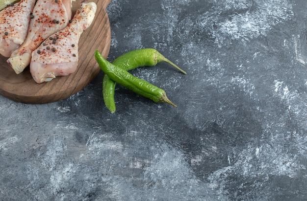 Groene paprika met kippenbenen over grijze achtergrond.