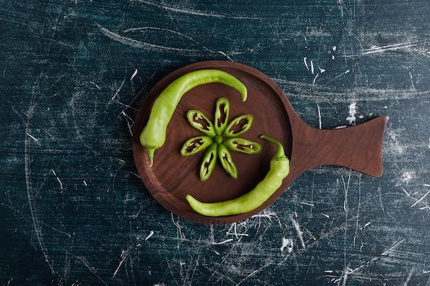 Groene paprika plakjes in bloemvorm op een houten bord.