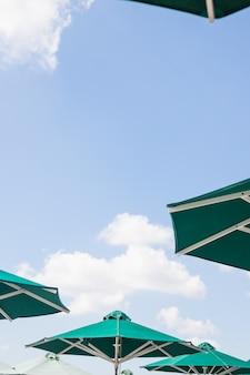 Groene paraplu's op blauwe hemel met wolken in de zomer