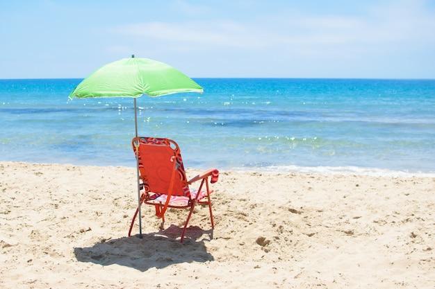 Groene parasol en rode chaise lounge op het zandstrand tegen de blauwe zee costa blanca van spanje en lucht.