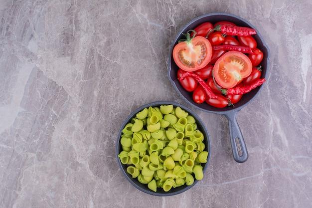 Groene pasta's met rode tomaten en spaanse pepers in een pan