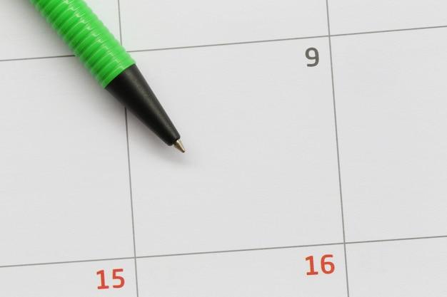 Groene pen wordt op de 9e dag op de kalender geplaatst en heeft kopieerruimte.