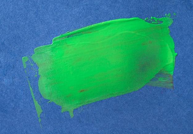 Groene penseelstreek op blauwe achtergrond