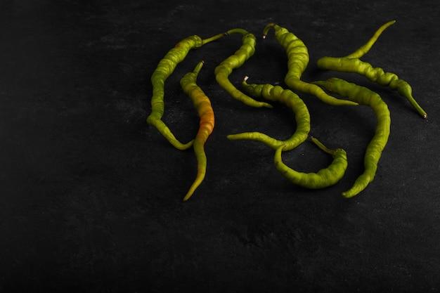 Groene pepers geïsoleerd op zwart oppervlak.