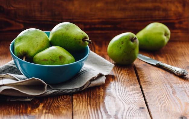 Groene peren in blauwe kom en enkele peren op achtergrond met mes.