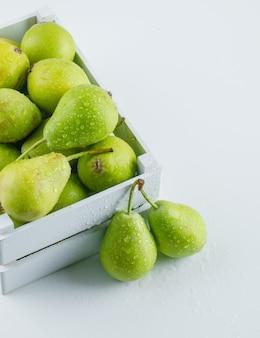 Groene peren in een houten doos hoge hoek bekijken op een witte tafel