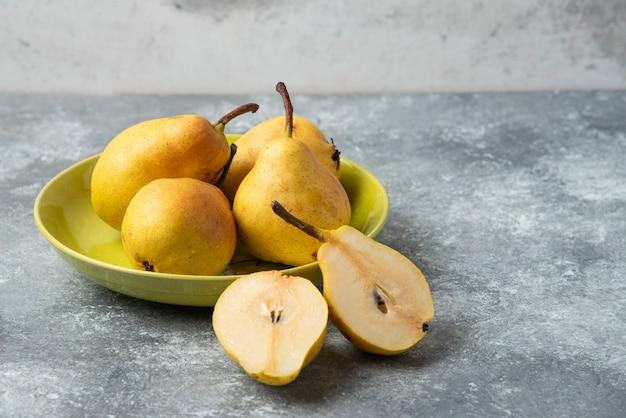 Groene peren in een keramische plaat.