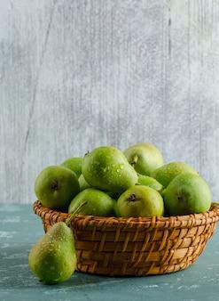 Groene peren in een mand op gips en grungy muur. zijaanzicht.
