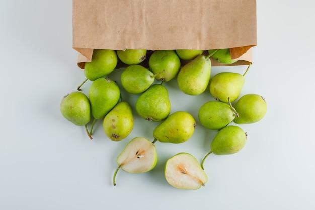 Groene peren in een papieren zak plat lag op een witte tafel