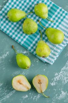 Groene peren op gips en keuken handdoek. plat lag.
