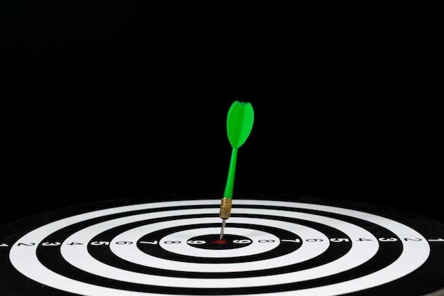 Groene pijl raakt in het midden van het dartbord