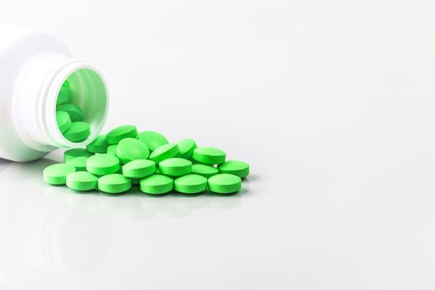 Groene pillen zijn verspreid uit een pot op wit.