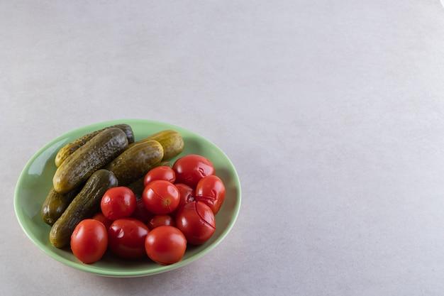 Groene plaat van ingelegde komkommers en tomaten op stenen tafel.