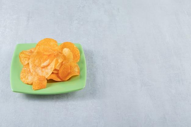 Groene plaat van pittige chips op steen geplaatst.
