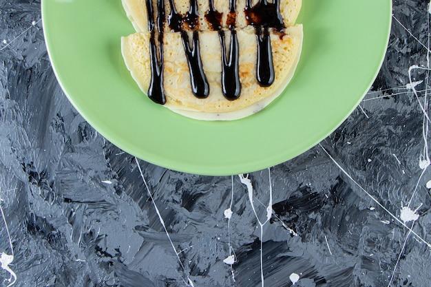 Groene plaat van zelfgemaakte pannenkoeken met chocoladebovenste laagje op marmeren oppervlakte.