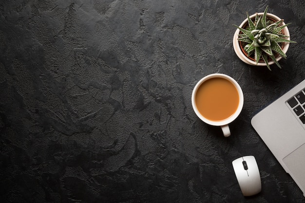 Groene plant in een pot, kopje koffie, computermuis en moderne zilveren laptop op donkere achtergrond.