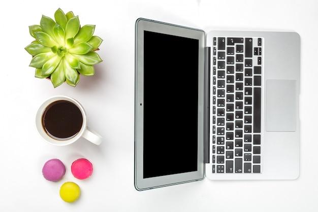 Groene plant in een pot, kopje koffie, kleurrijke bitterkoekjes en moderne zilveren laptop op witte achtergrond