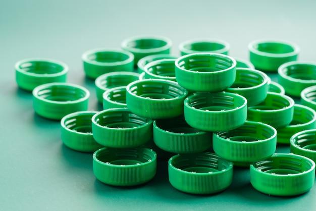 Groene plastic doppen van flessen op de backgraund