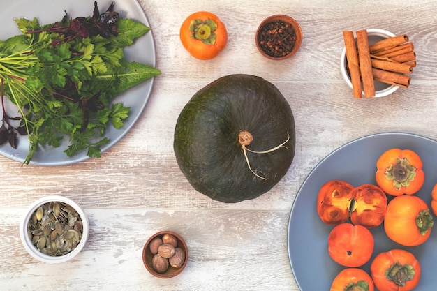 Groene pompoen, dadelpruimen en ingrediënten voor het smakelijke vegetarische koken op lichte houten oppervlakte