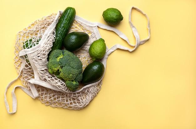 Groene producten in een herbruikbare zak op een gele achtergrond