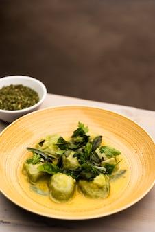 Groene raviolideegwaren die in plaat met kom van kruiden worden gediend