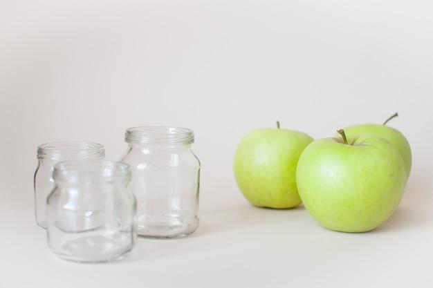 Groene rijpe appels en lege transparante potten voor babyvoeding op grijs.