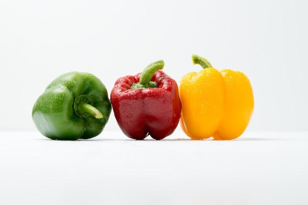 Groene, rode en gele paprika op witte tafel en wit.