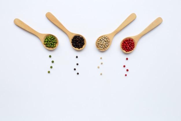 Groene, rode, witte en zwarte peperbollen met houten lepel op wit