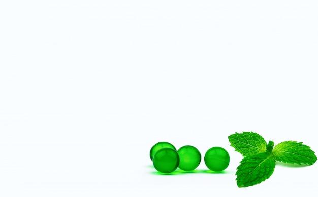 Groene ronde zachte capsulepillen en muntbladeren met exemplaarruimte
