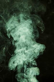 Groene rook die op zwarte achtergrond wordt uitgespreid