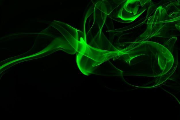 Groene rooksamenvatting op zwarte achtergrond, duisternisconcept
